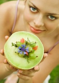 Young woman holding up melon bowl of fruit