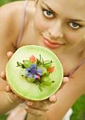 Junge Frau hält halbe Melone mit Stachelbeeren