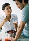 Woman holding up spoon of tomato sauce for man to taste