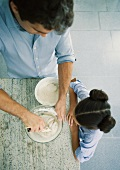 Girl watching as father mixes dough, high angle view