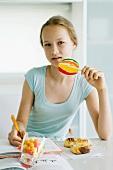 Mädchen isst Süssigkeiten bei den Hausaufgaben