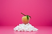 Food concept, fresh peach on top of pile of sugarcubes