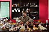Cafe owner, assorted pastries and baked goods on counter