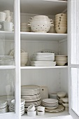 A view of vintage crockery through an open cupboard door