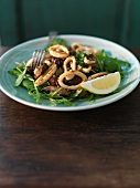Squid rings with mushrooms, rocket and olives