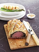 Fillet Wellington on a wooden chopping board with carving cutlery