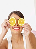 Woman holding orange slices in front of her face