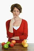 Thoughtful woman with apples and pears