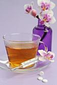 Tee, Fieberthermometer, Schüßler-Salze und Blume