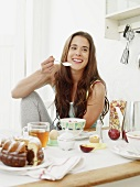 Smiling young woman having breakfast