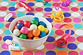 A Bowl of Colorful Gumballs on a Polk-a-Dot Table Cloth with Scattered Party Ribbons
