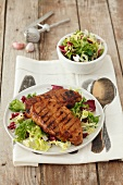 Grilled pork neck steaks on a bed of salad