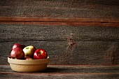 A Bowl of Assorted Apples in a Rustic Setting