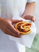 A girl holding a spicy pastry on a paper napkin