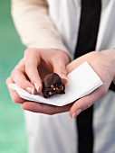 A woman holding a Rocky Road truffle praline