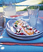 Salmon Filet with Nectarine and Serrano Chili Salsa; On a Plate on an Outdoor Table; With Lemonade