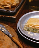 A Piece of Leek and Asparagus Strudel on a Metal Plate; Knife