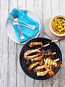 Prawn kebabs on a barbecue with mango salsa