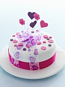A celebratory cake decorated with hearts