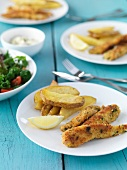 Fish fillets with a parmesan and lemon coating and potato wedges