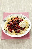 A sweet pasta dish with warm berries, vanilla ice cream and cinnamon