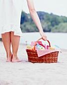 Frau mit Picknickkorb am Strand
