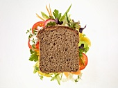 A slice of wholemeal bread on a bed of vegetables