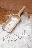 The word FLOUR written in flour with a wooden scoop
