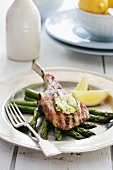 Veal chop with basil butter on a bed of green asparagus