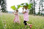 Zwei blonde Mädchen mit Rhabarberblättern als Sonnenschirme im Garten