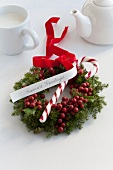 A Christmas wreath made of holly berries and conifers decorated with a candy cane