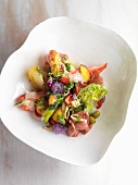 Tomato salad with ham, fruit and edible flowers