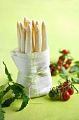 White asparagus wrapped in a tea towel and cocktail tomatoes