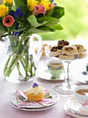 A table laid with a bunch of flowers, cupcakes and tea