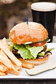 Hamburger with French Fries,  a Pickle and a Glass of Stout Beer