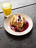 Serving of Baked French Toast with Whipped Cream and Berry Sauce; Glass of Orange Juice