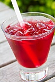 Absolute Vodka and Cranberry Juice Cocktail in a Glass with Ice and a Straw; Outdoors