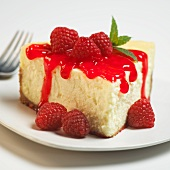 Slice of Cheesecake with Raspberry Sauce; On a White Plate; Close Up