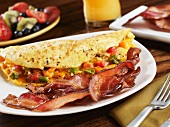 Strips of Smoked Bacon with a Veggie Omelet on a White Dish' Fruit Salad and Orange Juice