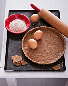 Pie pasty with ingredients and a rolling pin