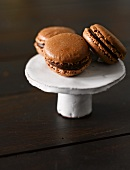 Three chocolate macaroons on a cake stand