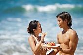 Asiatisches Pärchen isst Snack am Strand