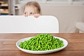 Girl hiding from peas at table