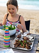 A girl having a picnic on a beach with salad and barbecued meat