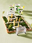 A football pitch-shaped pizza topped with spinach, cheese and baby corn cobs