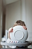 Toddler sitting in high chair, holding plate in front of face