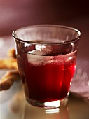 Elderberry syrup in a glass with ice cubes