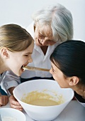 Grandmother baking with granddaughters, one girl tasting batter
