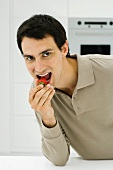 Man eating strawberry, looking at camera, close-up