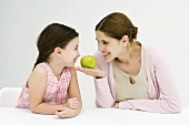 Mother and daughter sitting face to face, smiling at each other, woman holding apple
